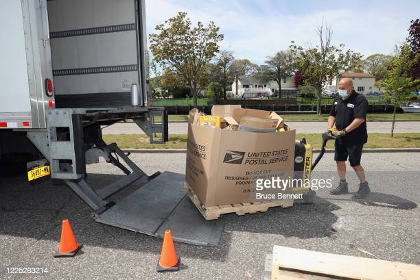 Volunteers accept donated goods for those in need from during a cruisethrough food drive organized by the Town of Oyster Bay and Island Harvest at...