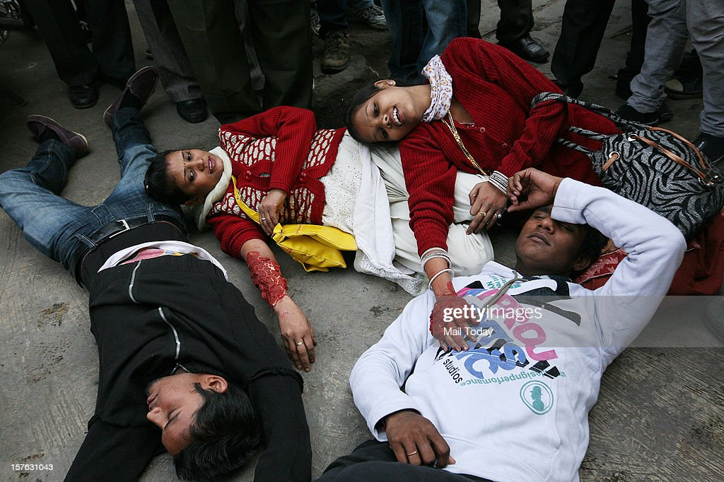 Volunteers acting as bomb blast victims wait for rescue operation during a mock security drill as part of Delhi Emergency Management Exercise (DEMEX) in New Delhi on Tuesday.