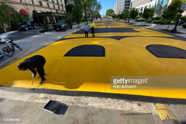 Volunteers add a new coat of paint to the Black Lives Matter sign which runs two city blocks near the White House on what was part of 16th Street but...