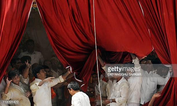Volunteers and devotees remove curtains after the final rituals of the burial of Hindu guru Sathya Sai Baba inside Prashanthi Nilayam in the village...