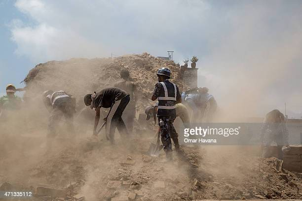 Volunteers and emergency workers search for bodies buried under the debris of one of the temples at Basantapur Durbar Square on April 27, 2015 in...