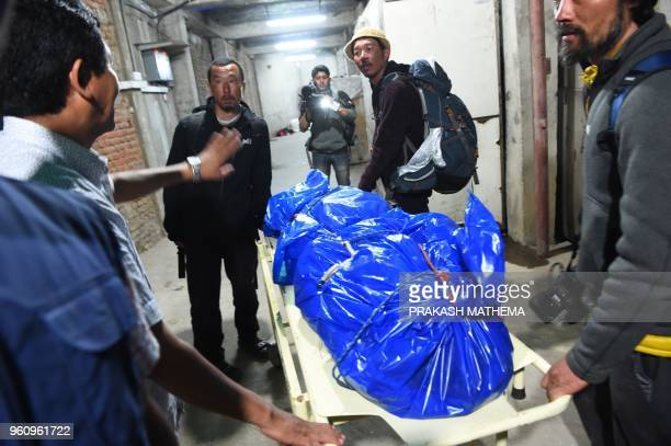 Volunteers and friends carry the body of Japanese climber Nobukazu Kuriki on a stretcher at a hospital in Kathmandu on May 21 2018 A Japanese climber...