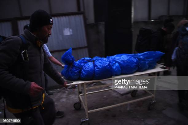 TOPSHOT Volunteers and friends carry the body of Japanese climber Nobukazu Kuriki on a stretcher at a hospital in Kathmandu on May 21 2018 A Japanese...