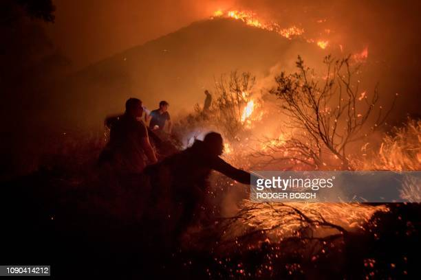 Volunteers and local residents use wet towels to fight one front of a large brush fire that started around the mountains in the city centre on...