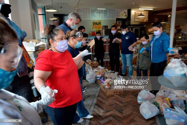 Volunteers and members of the Chelsea Collaborative Inc pray before distributing food and packages of donated goods to people in need at the Pan Y...