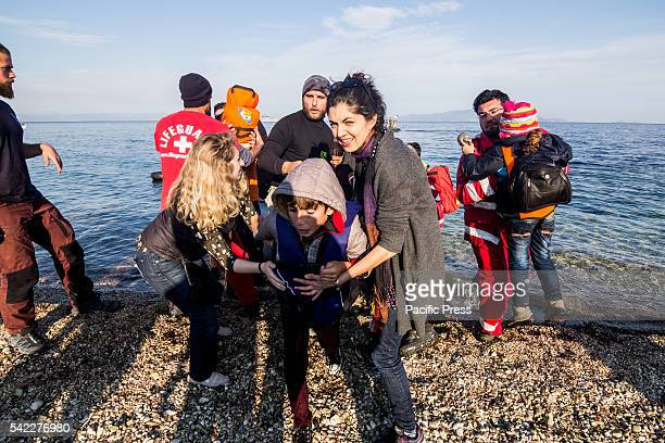 Volunteers and NGO members help a young Afgan migrant boy to disembark from a rubber boat after he has crossed the Aegean Sea with 45 other people...