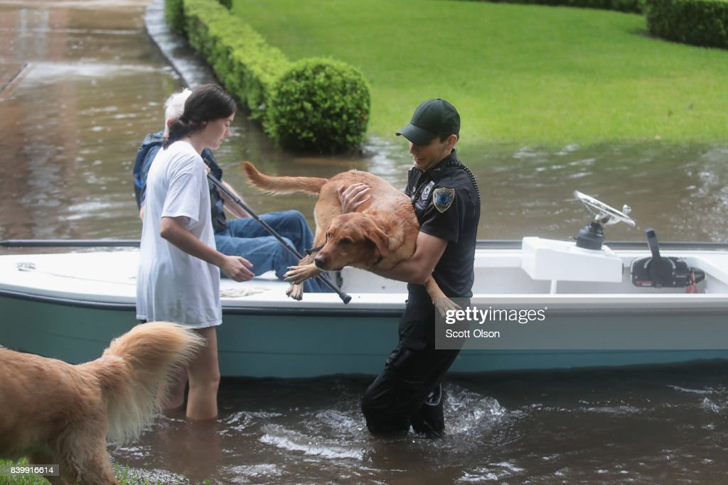 Volunteers and officers from the neiborhood security patrol help to rescue residents and their dogs in the upscale River Oaks neighborhood after it was inundated with flooding from Hurricane Harvey on August 27, 2017 in Houston, Texas. Harvey, which made landfall north of Corpus Christi late Friday evening, is expected to dump upwards to 40 inches of rain in Texas over the next couple of days.