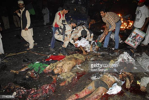 Volunteers and paramilitary soldiers tend to the bodies of a Pakistani people party activists laying in the street after a powerful suicide car bomb...