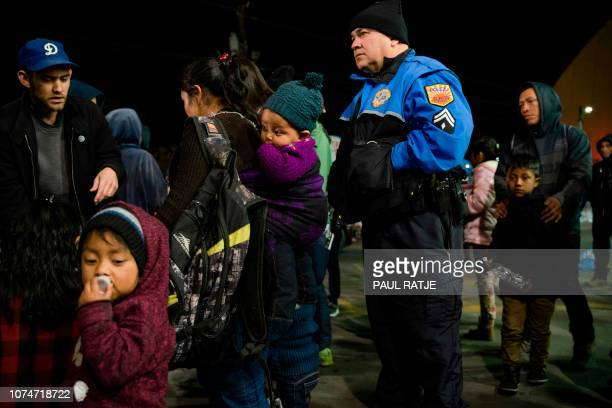 Volunteers and police help organize a large group of asylum seekers outside a Greyhound Station after they were dropped off by Immigration and...
