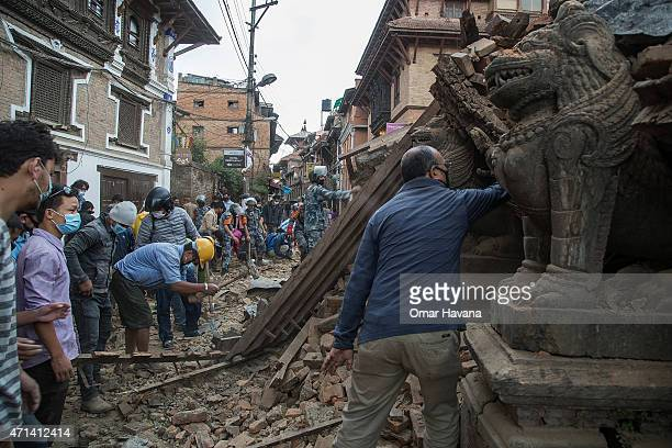 Volunteers and quake rescue team members clear the debris from a collapsed temple near Patan Durbar Square on April 28, 2015 in Lalitpur, Nepal. A...