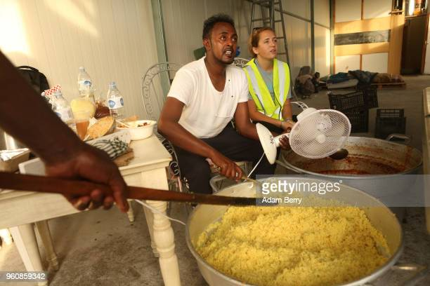 Volunteers and refugees prepare bags of hot beans and rice at an independent NGOrun food distribution center outside the Moria refugee camp on May 20...