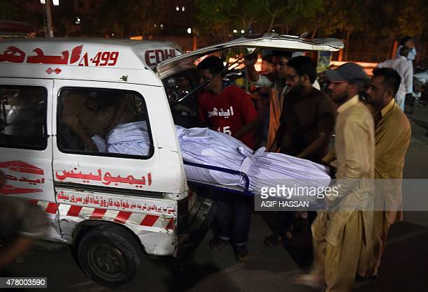 EDHI volunteers and relatives shift the dead body of a heatwave victim into an ambulance at the EDHI morgue in Karachi on June 21 2015 A heatwave has...