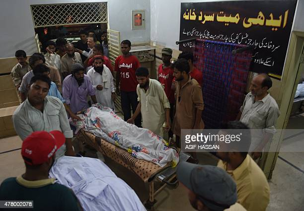 EDHI volunteers and relatives shift the dead body of heatwave victims at the EDHI morgue in Karachi on June 21 2015 A heatwave has killed at least 45...