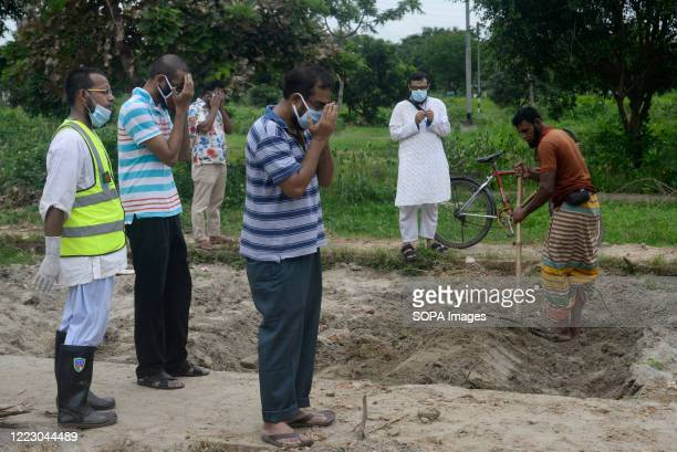 Volunteers and relatives wearing face masks as a precaution pray during a funeral of a deceased Coronavirus victim. Bangladesh has recorded a total...