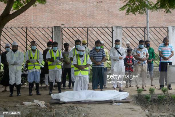 Volunteers and relatives wearing face masks as a precaution pray near the body of a coronavirus victim before the burial. Bangladesh has recorded a...