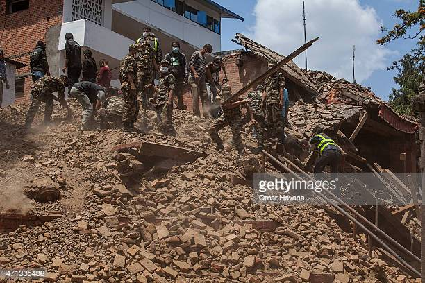 Volunteers and rescue team members clear debris of a collapsed temple at Basantapur Durbar Square on April 27, 2015 in Kathmandu, Nepal. A major 7.8...