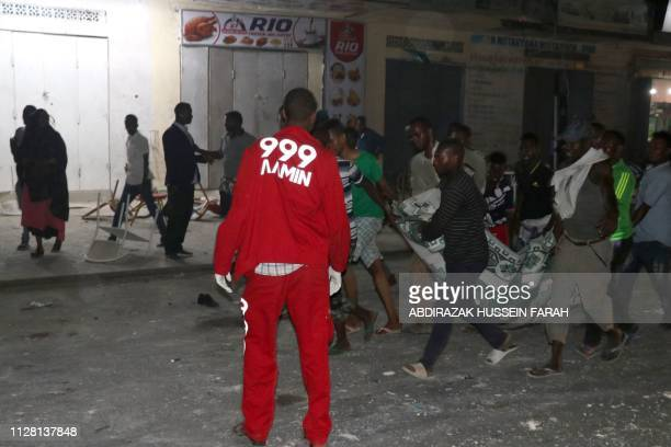 Volunteers and rescue workers evacuate an injured victim outside the Maka AlMukarama hotel in the Somalia capital Mogadishu on February 28 2019 after...