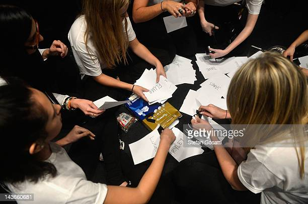 Volunteers and stylists orgainse models names backstage ahead of the Mens Show on day three of MercedesBenz Fashion Week Australia Spring/Summer...