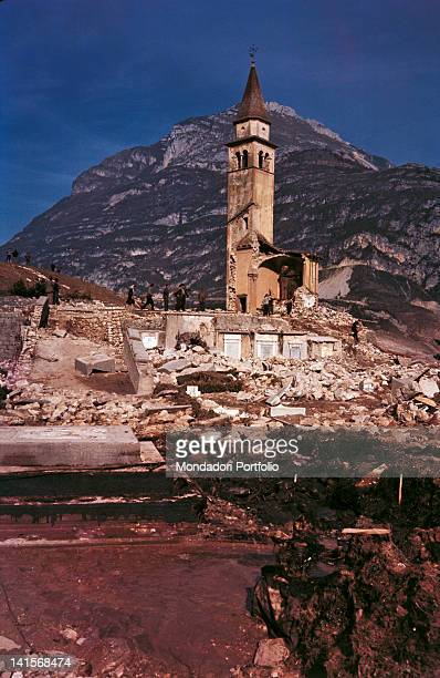 Volunteers and survivors to the disaster of Vajont dam in front of the tower of Saint Thomas church in Pirago surprisingly survived while the rest of...