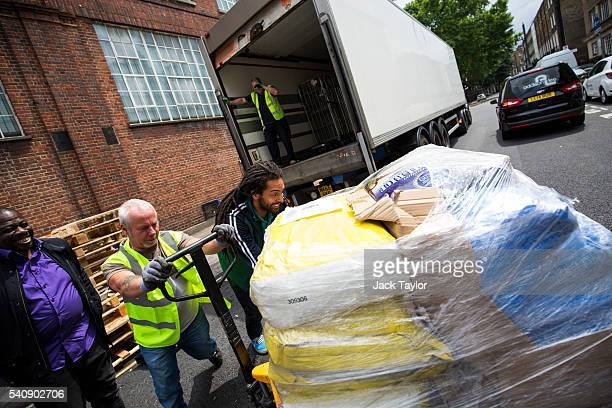Volunteers and workmen load aid for refugees and migrants living in Calais onto a truck outside Access Self Storage on June 17 2016 in London England...