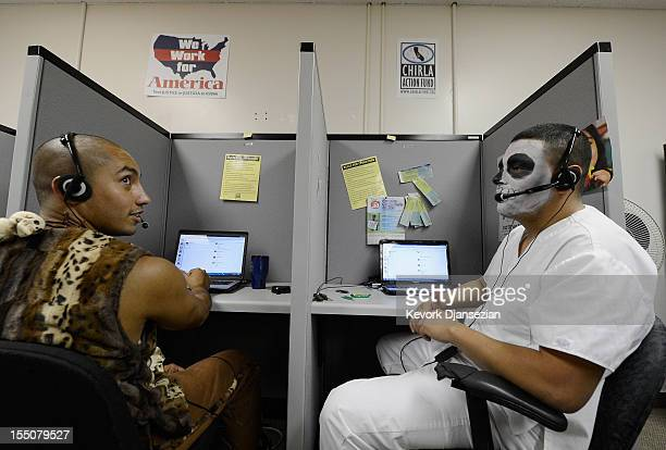 Volunteers Angel Zuniga and Marvin Giron of Coalition for Humane Immigrant Rights of Los Angeles are dressed in Halloween costumes while conducting a...