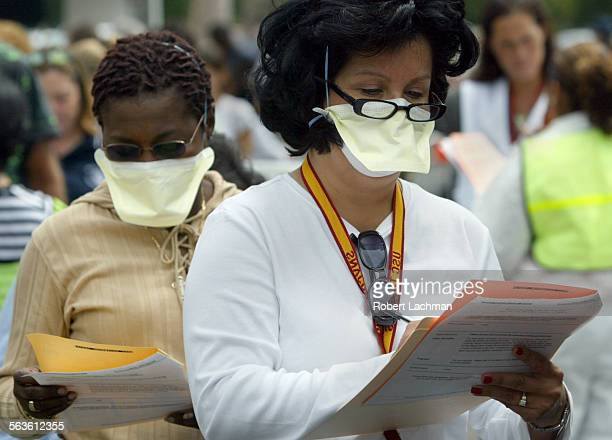 Volunteers Anita Bolden and Linda Lopez fill out forms as they participate in the small pox immunization drill at the Crystal Cathedral in Garden...