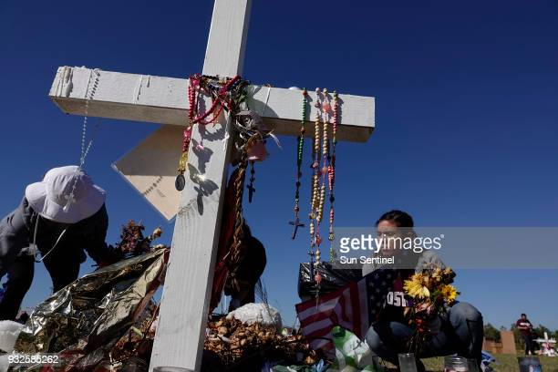 Volunteers Annabelle Andon left and Joanna Polk remove items left at the memorials for the Marjory Stoneman Douglas High School shootings Thursday...