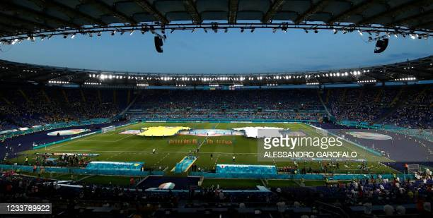 Volunteers appear on the pitch with giant replicas of the Ukraine and the England jerseys ahead of during the UEFA EURO 2020 quarter-final football...