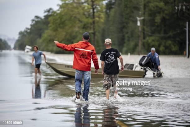 Volunteers approach a boat in need of assistance on a highway following Tropical Storm Imelda in Fannett Texas US on Friday Sept 20 2019 The remnants...