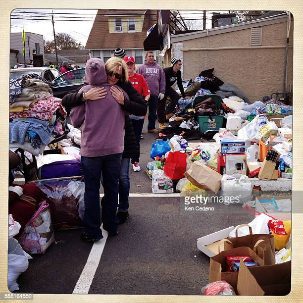 Volunteers are hugged from members of the local community who donated goods for families in need who were severely affected by Superstorm Sandy in...