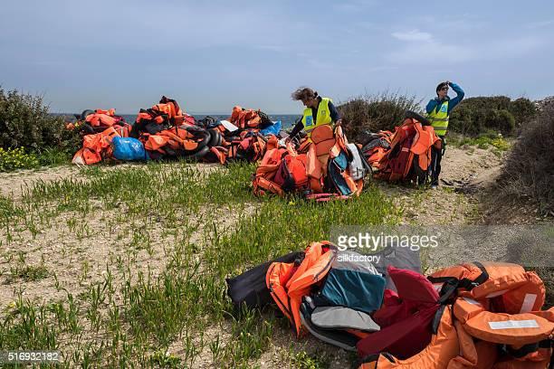 Les bénévoles sont la suppression des réfugiés vestes de vie grecque à gauche sur la plage