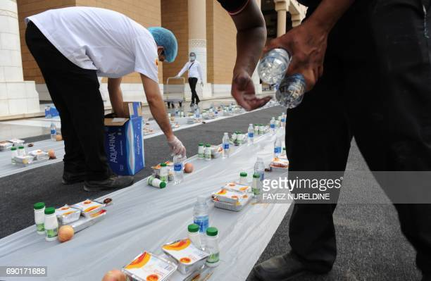 Volunteers arrange food and drink in preparation for the a meal known as the 'Iftar' where Muslims break their fast during the Muslim holy fasting...