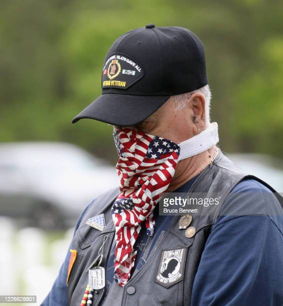 Volunteers arrive to place flags at the Calverton National Cemetery on May 23 2020 in Wading River New York The US Department of Veterans Affairs...