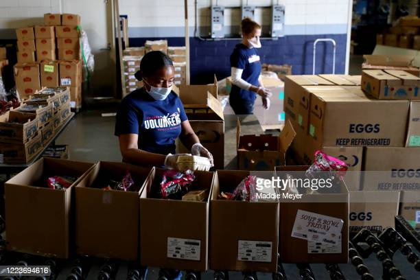 Volunteers assemble boxes of food for families as part of the SoupR Bowl at Gillette Stadium on May 08 2020 in Foxborough Massachusetts The Patriots...