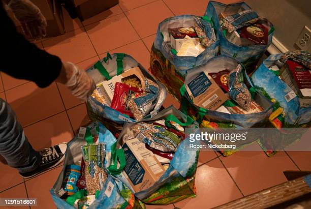 Volunteers assemble one of three bags of uncooked food given as donations to those in need at the Holy Apostles Soup Kitchen on December 15, 2020 in...