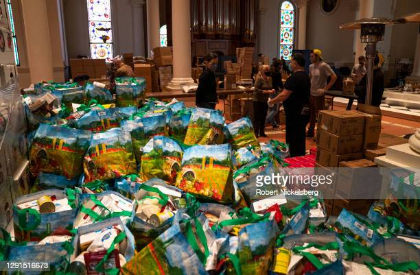 Volunteers assemble three bags of uncooked food given as donations to those in need at the Holy Apostles Soup Kitchen on December 15, 2020 in New...