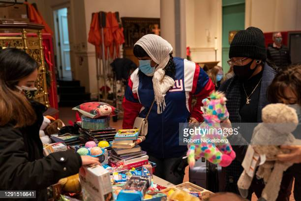 Volunteers assist people receiving a donated toy and uncooked food donations from the food pantry at the Holy Apostles Soup Kitchen on December 15,...