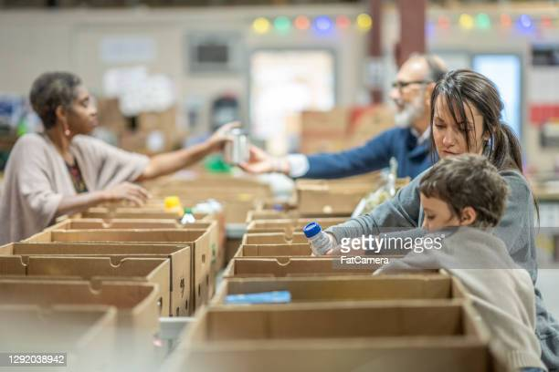 volunteers at a food bank - giving tuesday stock pictures, royalty-free photos & images