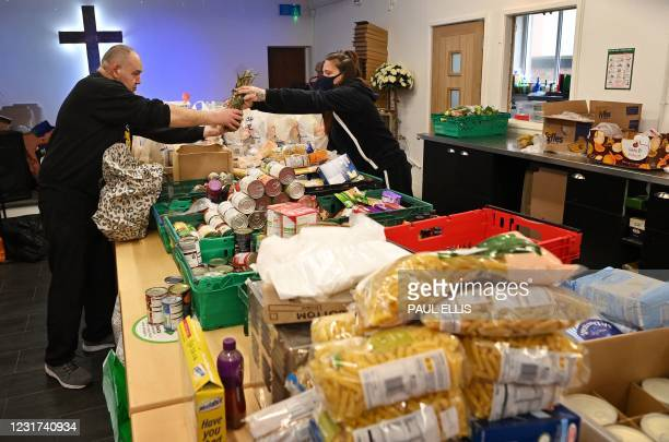 Volunteers at Amazing Graze Soup Kitchen in Blackpool, north west England on March 9, 2021 sort donated food to make food parcels. - In Britain's...