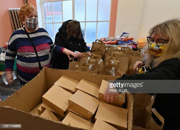 Volunteers at Amazing Graze Soup Kitchen in Blackpool, north west England, on March 9, 2021 make up bags with a hot meal and fresh fruit that are...