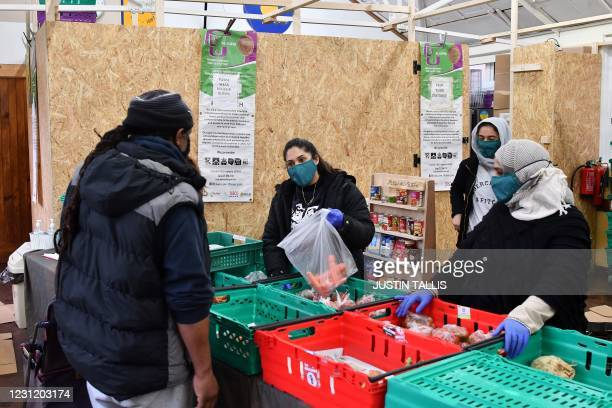 Volunteers at the PL84U Al-Suffa food bank serve a customer in Walthamstow in north east London on February 16, 2021. - A collaboration between...