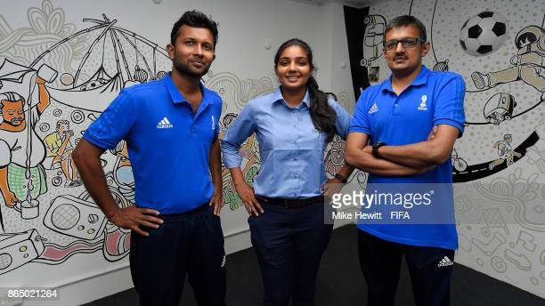 Volunteers Azeem Kattali and KR Harikrishnan with head volunteer Aisha Nazia stand in front of their artwork in the volunteers' centre at the...