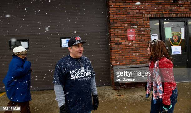 Volunteers Bernie DeMaio center and his wife Lesa right greet voters showing up to place their ballots in a special election between Democratic...