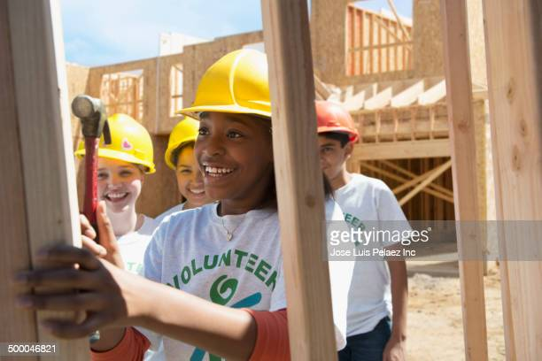 Volunteers building house together