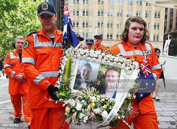 Volunteers carefully carry away a photo tribute of Katrina Dawson and Tori Johnson at Martin Place on December 23, 2014 in Sydney, Australia....