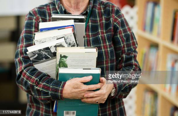 A volunteers carries a pile of books while populating the shelves of Twice Told Tales bookstore's new location on Maine Street in Brunswick on...