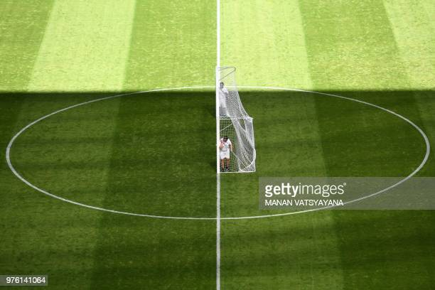 TOPSHOT Volunteers carry a goalpost to the centre of the pitch for Costa Rica's training session at the Samara Arena in Samara on June 16 2018 on the...