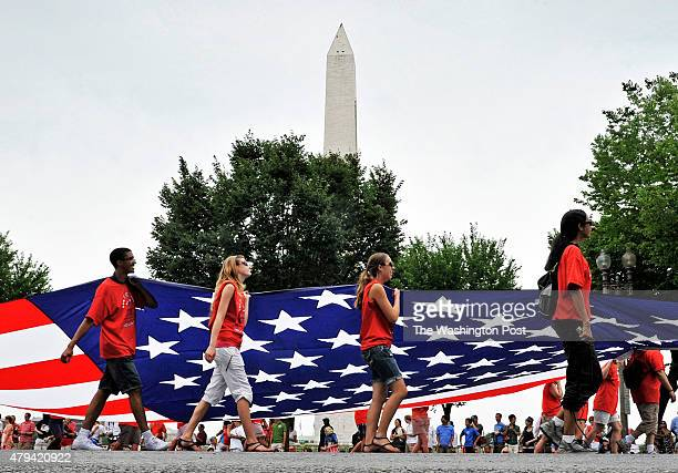Volunteers carry a huge American flag along the National Independence Day parade route down Constitution avenue on July 2011 in Washington DC