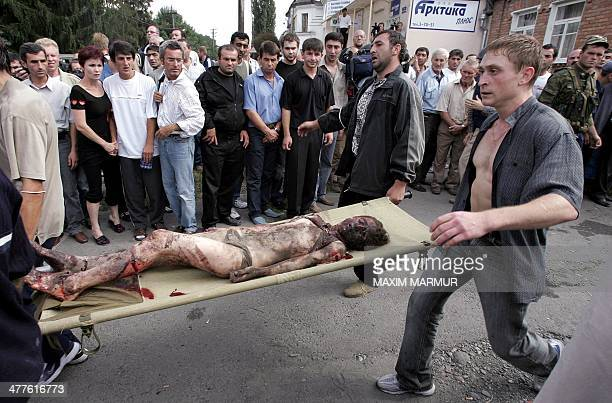 Volunteers carry an injured girl on a stretcher during the rescue operation of Beslan's school northern Ossetia 03 September 2004 Dozens of corpses...