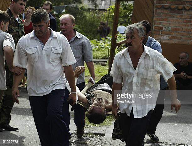 Volunteers carry an injured man after special forces stormed a school seized by Chechen separatists on September 3 2004 in the town of Beslan Russia...
